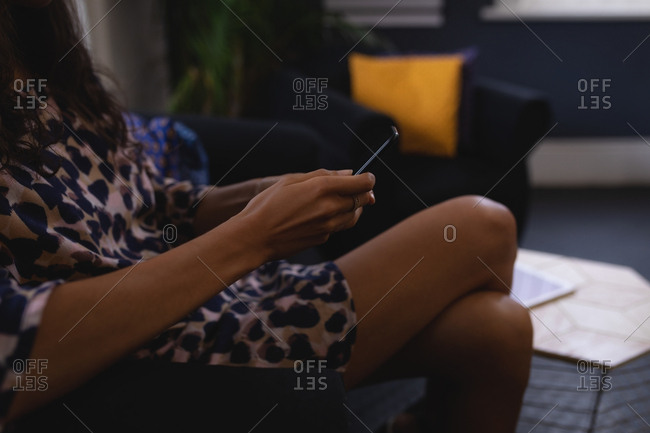 Mid section of mixed-race female executive using mobile phone while sitting on the sofa in the lobby at office