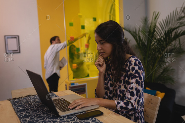 Side view of thoughtful mixed-race female executive working on laptop at desk in the office while business people discussing over sticky notes on glass wall