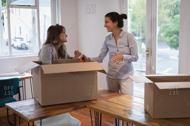 Side view of beautiful Diverse businesswomen packing cardboard boxes in the office