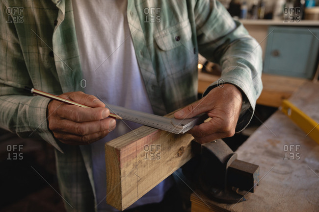 Mid section of mature Caucasian carpenter using try square on wooden plank in workshop