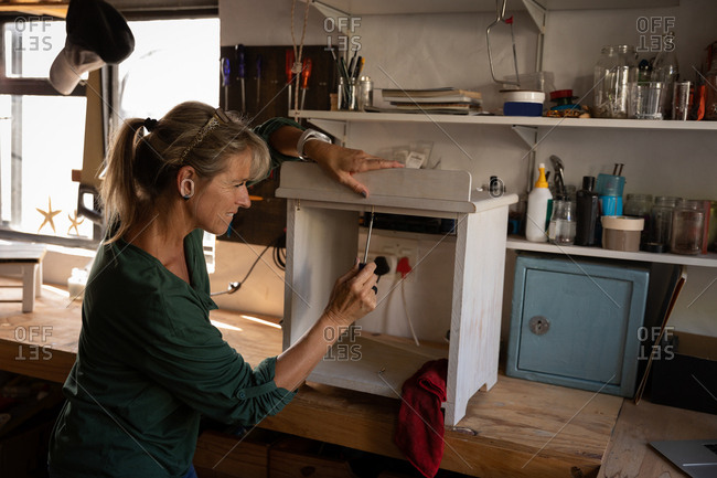 Side view of Caucasian female carpenter fixing cabinet in workshop