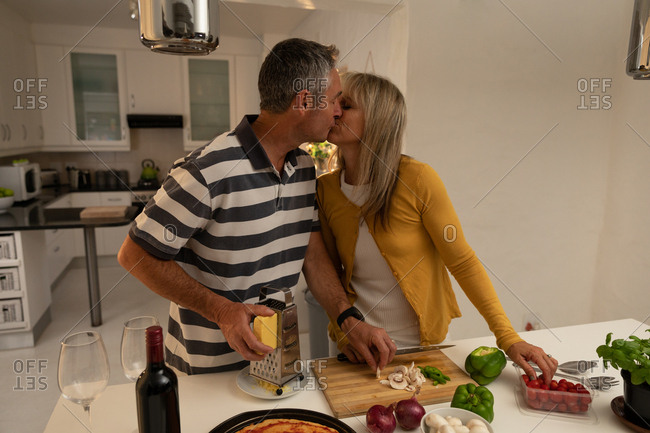 Front view of mature Caucasian couple kissing each other while preparing pizza in kitchen at home