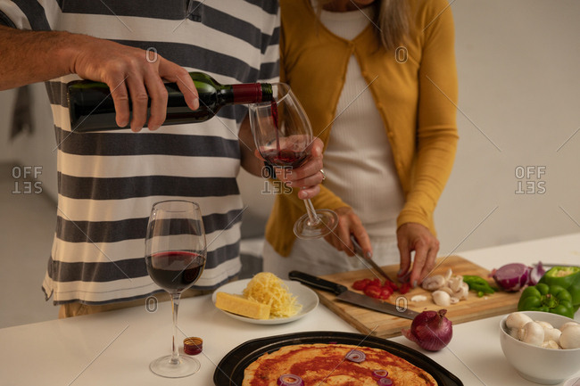 Mid section of Caucasian man pouring wine in glass while woman cutting vegetables and preparing pizza in kitchen at home