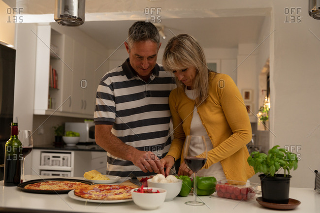 Front view of romantic mature Caucasian couple smiling while preparing pizza together in kitchen at home