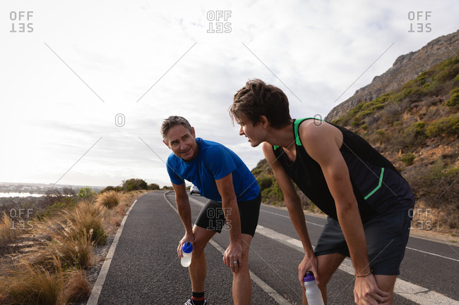 Side view of tired Caucasian father and son with water bottle standing on road