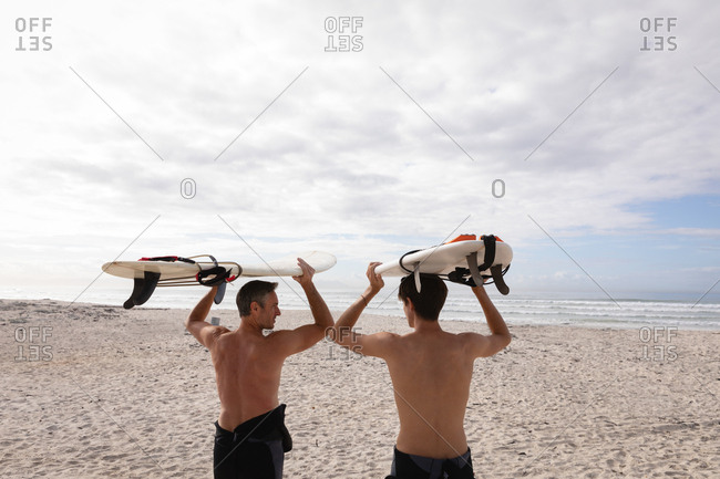 Rear view of Caucasian father and son standing with surfboard at beach