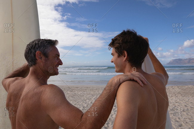 Rear view of Caucasian father and son with surfboard interact with each other at beach