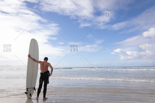 Rear view of Caucasian man standing with surfboard at beach on a sunny day