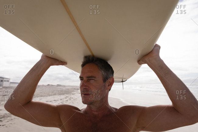 Close-up of mature Caucasian man standing with surfboard at beach on a sunny day