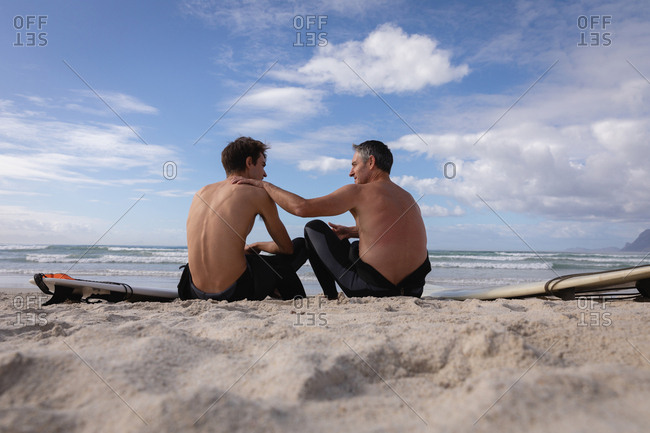 Rear view of Caucasian father and son with surfboard interact with each other