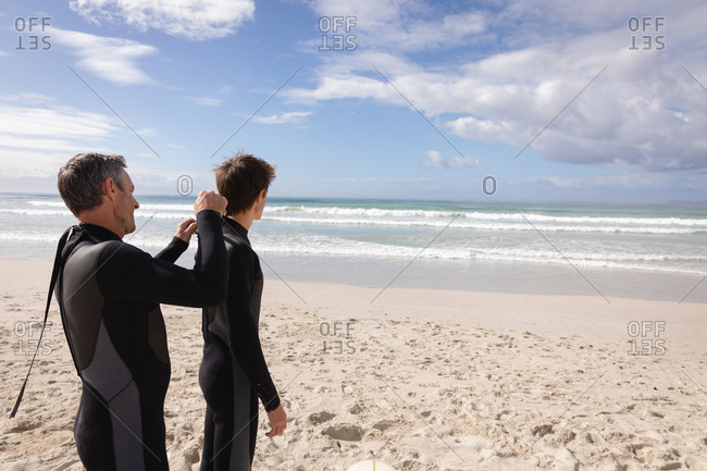 Rear view of Caucasian father assist son to wear wetsuit at beach on a sunny day