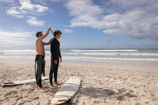 Side view of Caucasian father assist son to wear wetsuit at beach on a sunny day