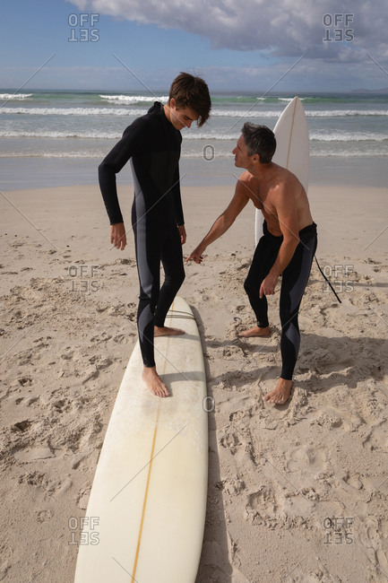 Front view of Caucasian father assist son to ride surfboard at beach on a sunny day