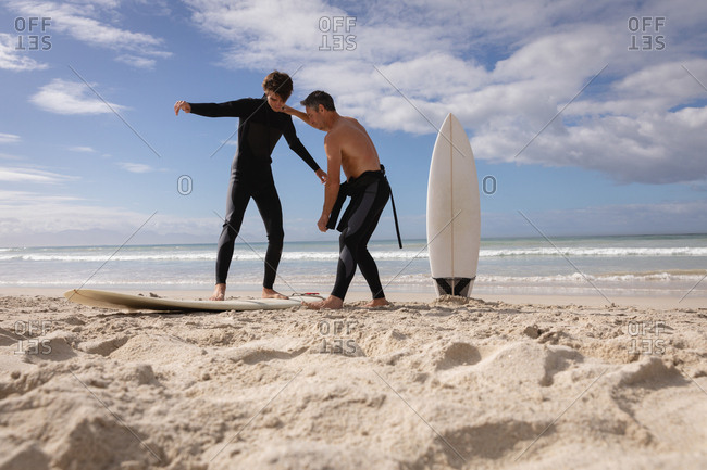 Low angle view of Caucasian father assist son to ride surfboard at beach on a sunny day