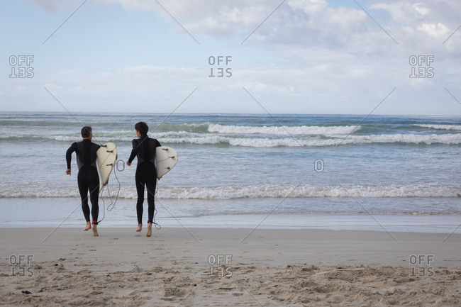 Rear view of Caucasian father and son with surfboard running towards sea