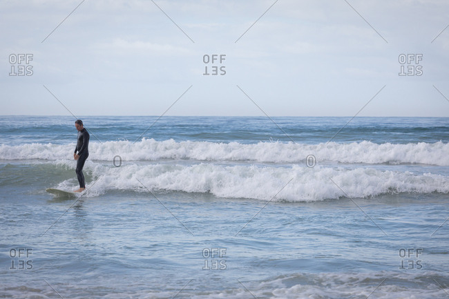 Front view of carefree Caucasian  man with surfboard surfing in the sea