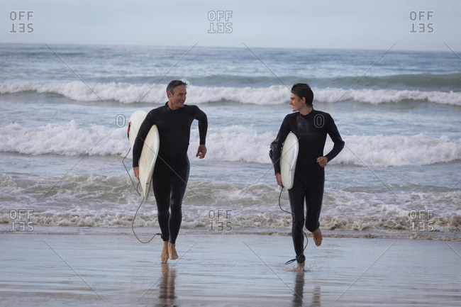 Front view of happy Caucasian father and son with surfboard running out of the sea