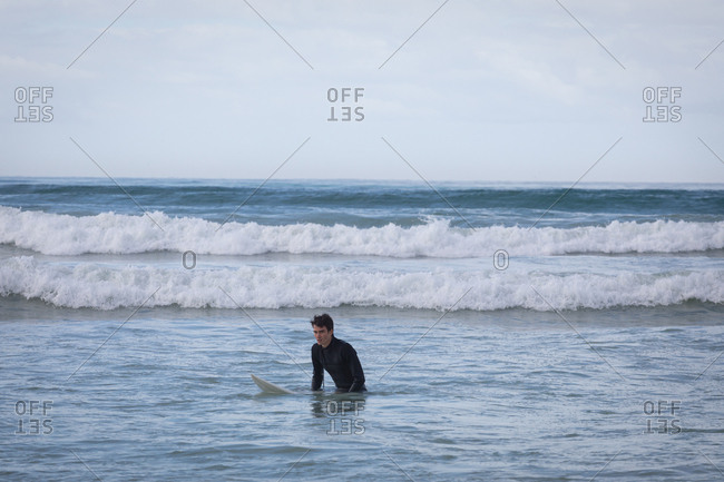 Front view of carefree Caucasian young man with surfboard surfing in the sea