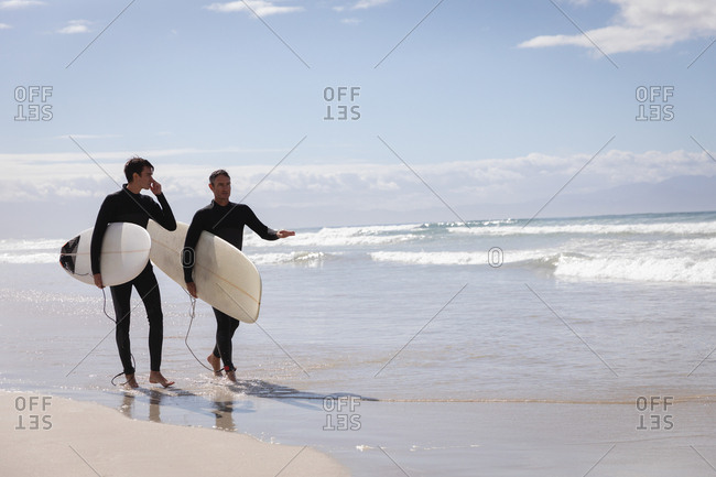 Side view of carefree Caucasian father and son with surfboard walking on beach