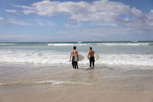 Rear view of Caucasian father and son with surfboard standing in sea