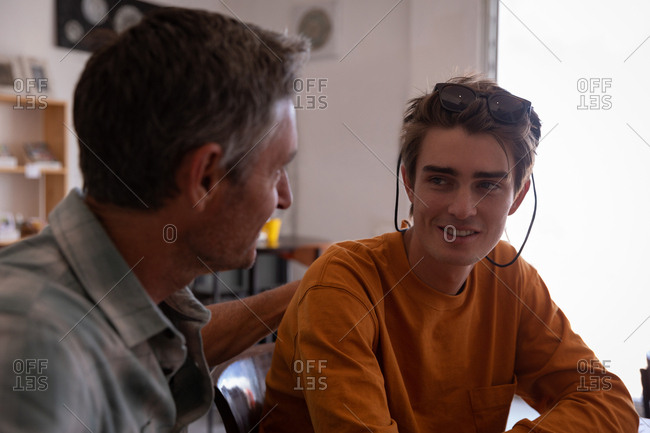 Side view of Caucasian father and son interact with each other at home
