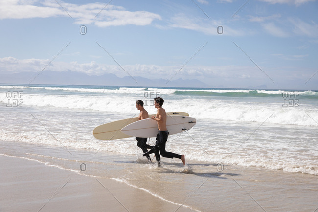 Side view of Caucasian father and son with surfboard running out of the sea on sunny day
