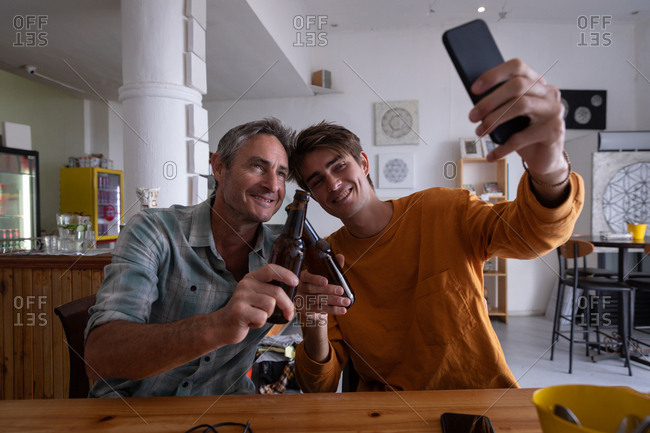 Front view of Caucasian father and son taking selfie from mobile phone while toasting beer at home