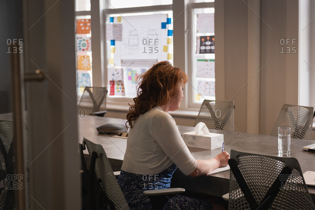 Rear view of Caucasian businesswoman writing on diary while sitting at table in office