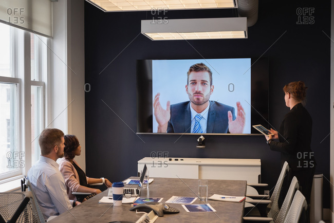 Rear view of diverse business executives doing video conferencing in business meeting at office