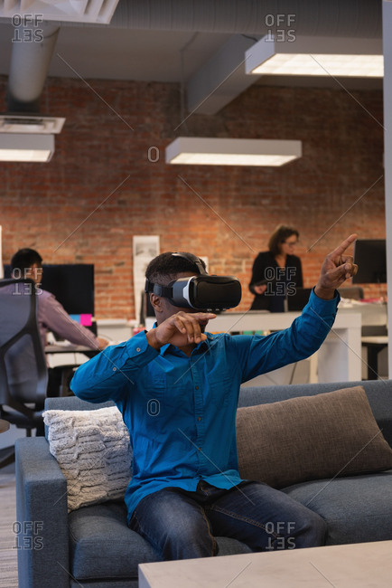 Front view of African-american businessman using virtual reality headset at the office