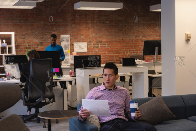 Front view of Asian businessman looking at document while having coffee in office