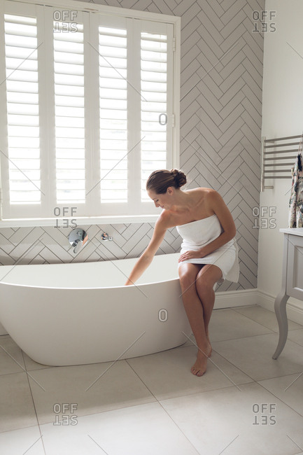 Beautiful woman checking the level of water in the bathtub in bathroom