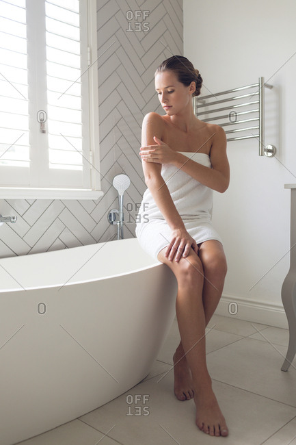 Beautiful woman applying lotion on her body in bathroom at home
