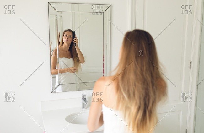Mirror image of beautiful woman comb her hair in bathroom at home