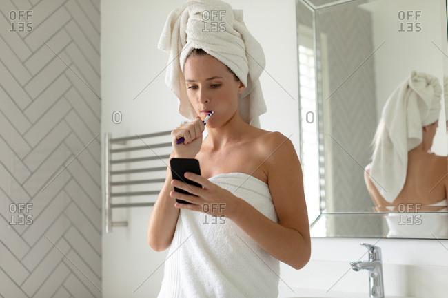 Beautiful woman using her phone while brushing her teeth in bathroom