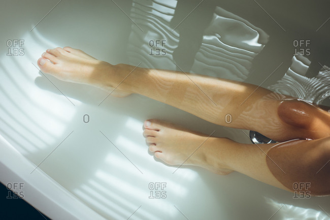 Close-up of woman's sexy legs in the bathtub in bathroom