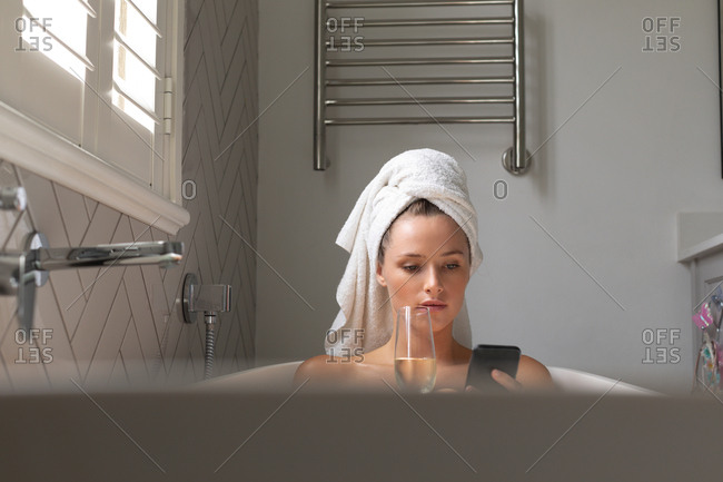 Beautiful woman having champagne and checking her phone in the bathtub at home