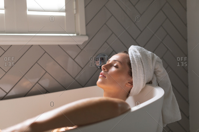 Beautiful woman relaxing in the bathtub in bathroom