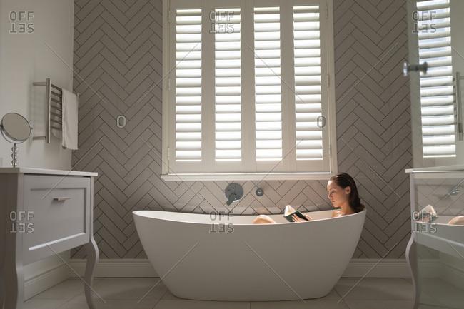 Beautiful woman reading a book in the bathtub in bathroom