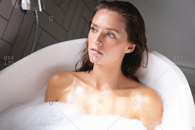 Thoughtful woman looking away while bathing in the bathtub in bathroom