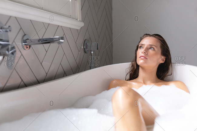Thoughtful woman bathing in the bathtub in bathroom at home