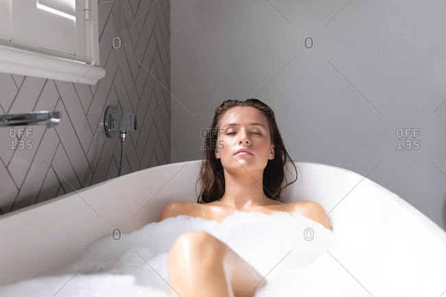 Beautiful woman relaxing while bathing in the bathtub in bathroom at home