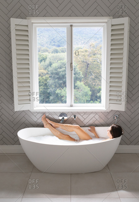 Woman relaxing in the bathtub in bathroom at home