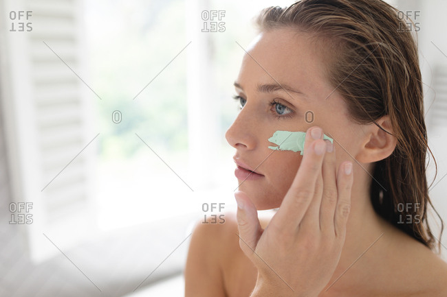 Close-up of woman applying facial mask after having bath
