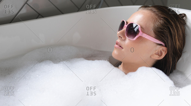Close-up of young woman wearing sunglasses relaxing in the bathtub