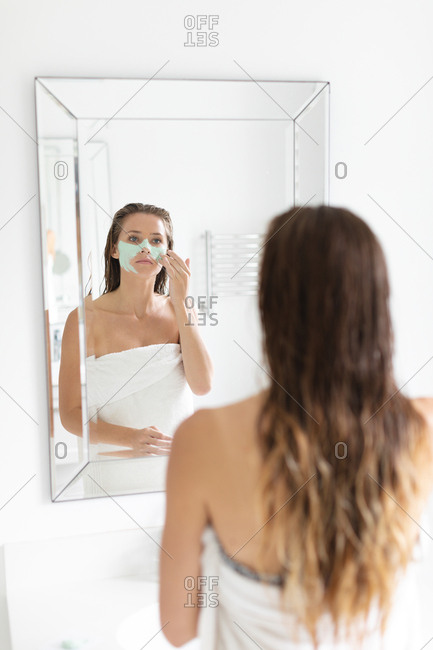 Rear view of woman looking in the mirror and applying facial mask after the bath