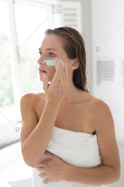 Close-up of woman applying facial mask after having bath