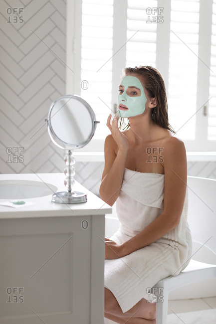 Woman looking in the mirror and applying facial mask after the bath in bathroom