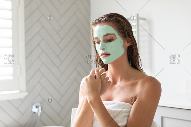 Close-up of thoughtful woman with facial mask sitting in the bathroom