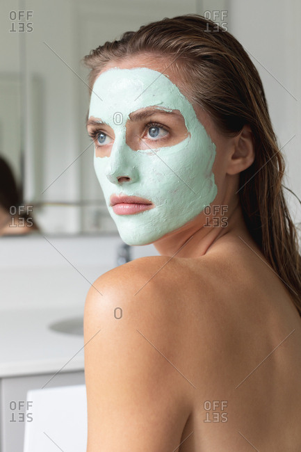 Close-up of woman in face mask looking away in the bathroom